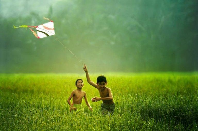 Em bé tung tăng thả diều trên cánh đồng lúa